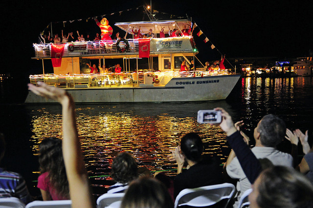 Corey Perrine/Staff Patrons aboard boat contestant 25, Double Sunshine, wave to the crowd Saturday, Dec. 8, 2012 on Naples Bay. The ship carried members of Naples Dollars for Buckeye Scholars supporters. Hundreds lined the shore to watch the annual event as boats were decked out in festive holiday lights and judged at the Naples Boating and Yacht Club for competition. Frank Perrucci, president of the Marine Industries Associations of Collier County, Inc. emceed the event. Judging included Mayor John Sorey. A total of 30 boats competed.